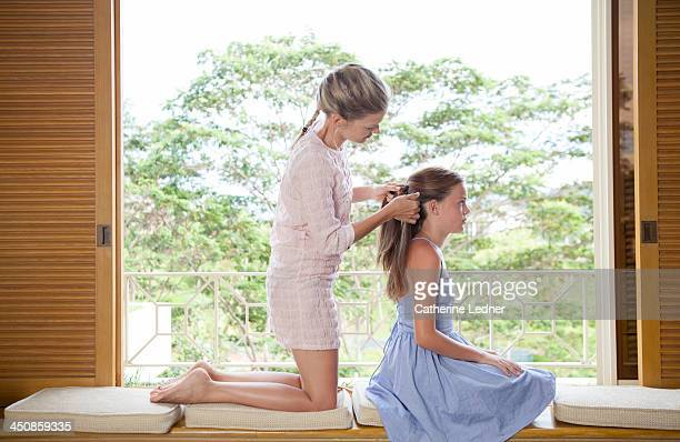 Mother doing daughter's hair