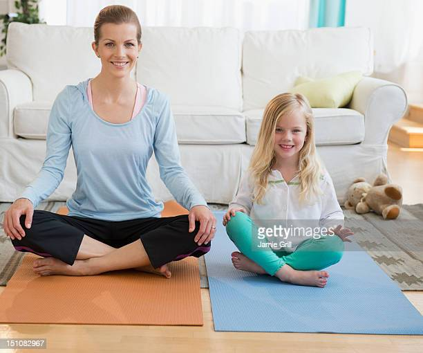 Mother doing yoga with daughter