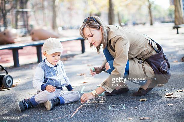 Mother drawing with son outdoors