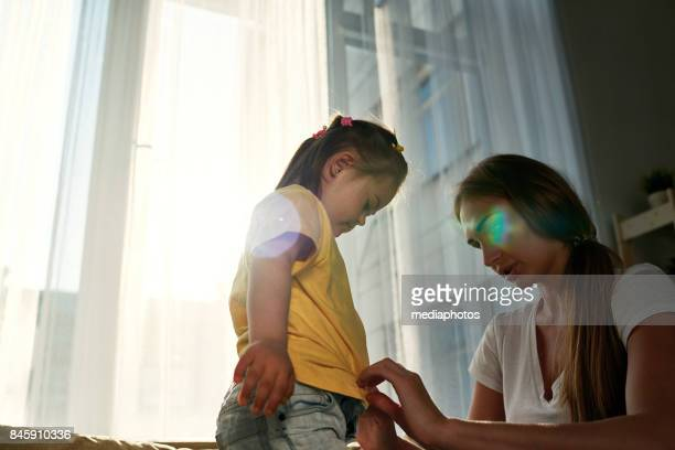 Mother dressing daughter at home