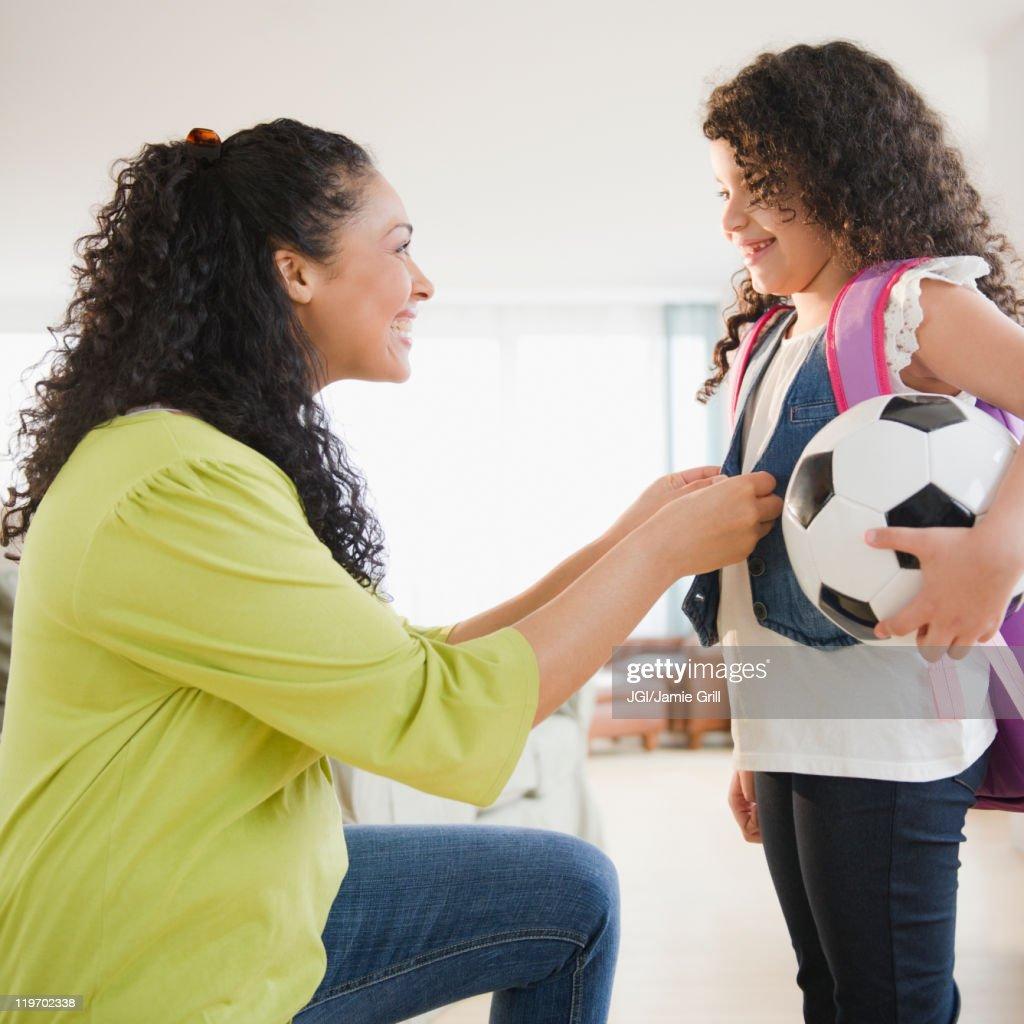 Mother dressing daughter holding soccer ball