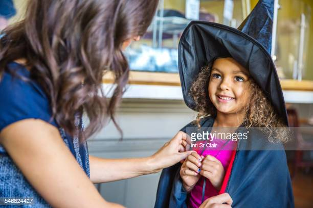 Mother dressing daughter in witch costume