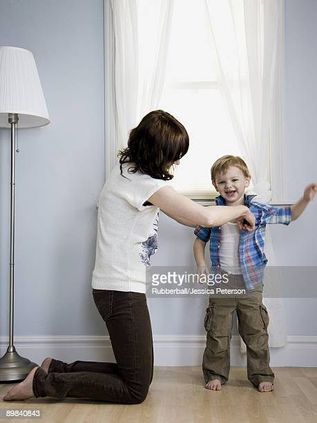 mother dressing her son