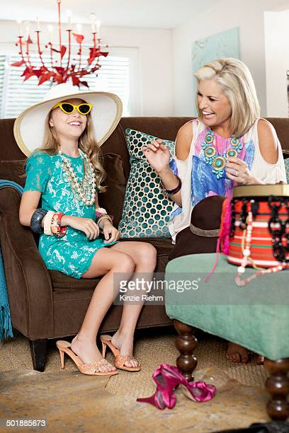 Mother dressing up daughter in hat and high heels