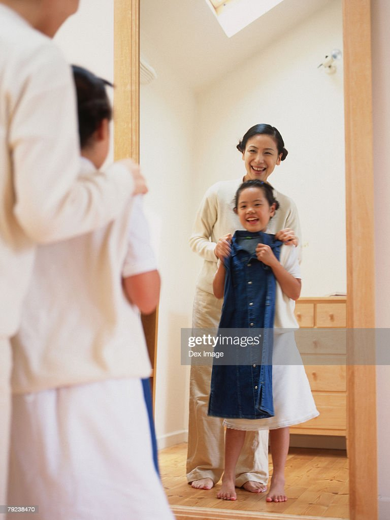 Mother dressing up laugher, looking in the mirror : Stock Photo
