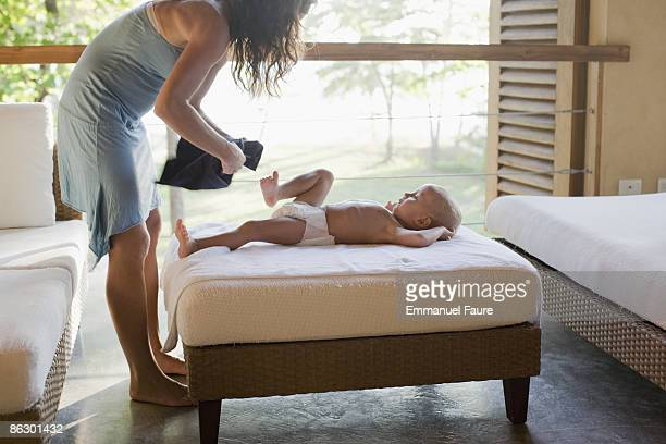 Mother dressing young child on vacation