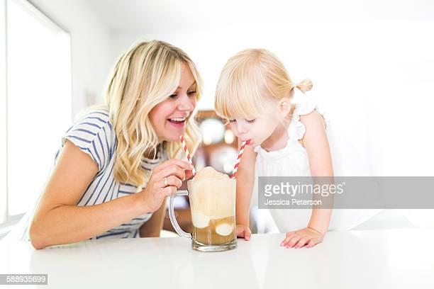 Mother drinking milkshake with daughter (2-3)