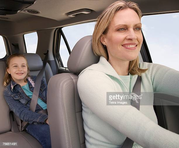 Mother driving car with daughter in back