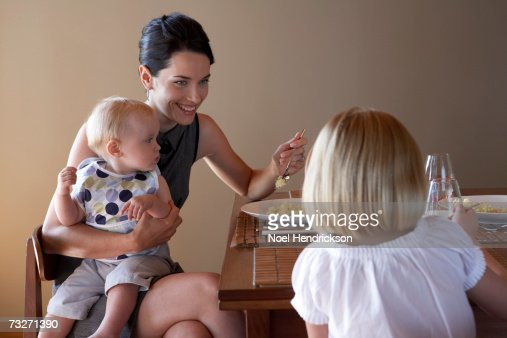 Mother eating with daughters (5-7) and (9-12 months) at table : Stock Photo