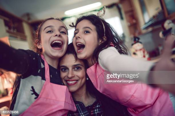 Mother Embraced with her Two Daughters Cooking Time Selfie