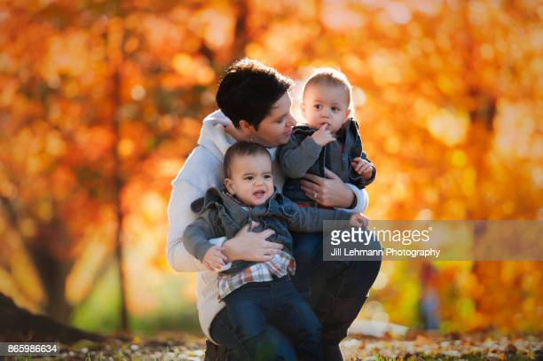 Mother Embraces Fraternal Twin Brothers at the Iowa State Campus in the Autumn Leaves full of color