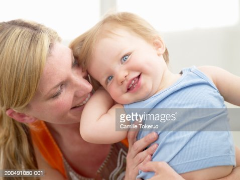 Mother embracing baby girl (12-15 months), smiling : Stock Photo