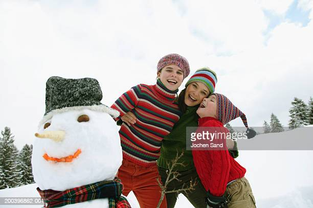 Mother embracing children (8-10) by snowman, smiling, portrait