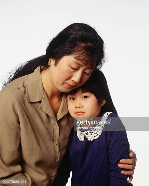 Mother embracing daughter (4-5), looking sorrowful