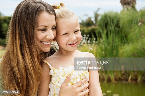Mother embracing daughter (4-5) outdoors : Stock Photo