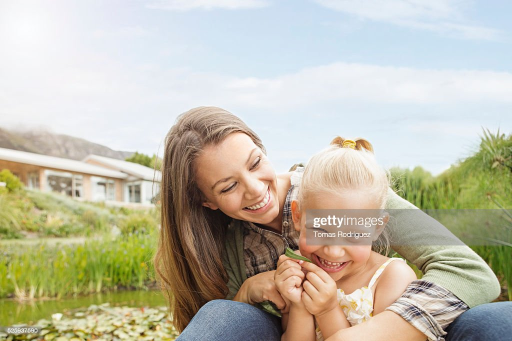 Mother embracing daughter (4-5) outdoors : Stock-Foto