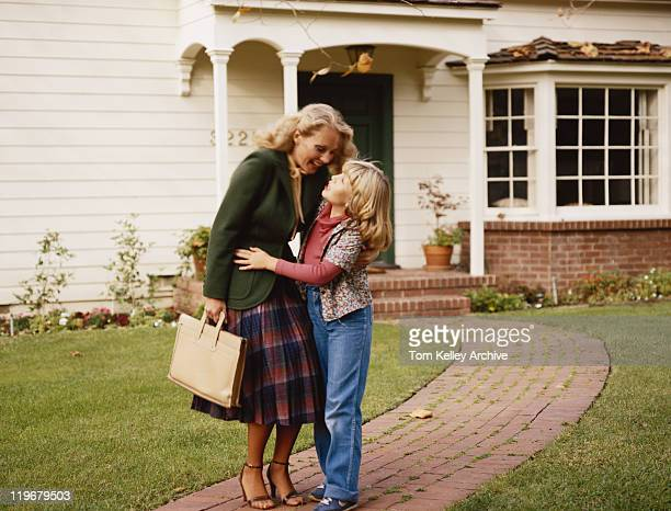 Mother embracing her daughter outside house on garden path