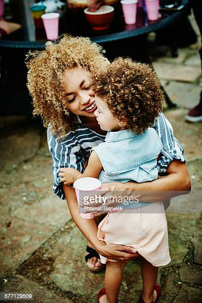 Mother embracing toddler daughter during party
