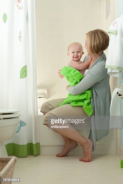Mother embracing toddler from bathtub.