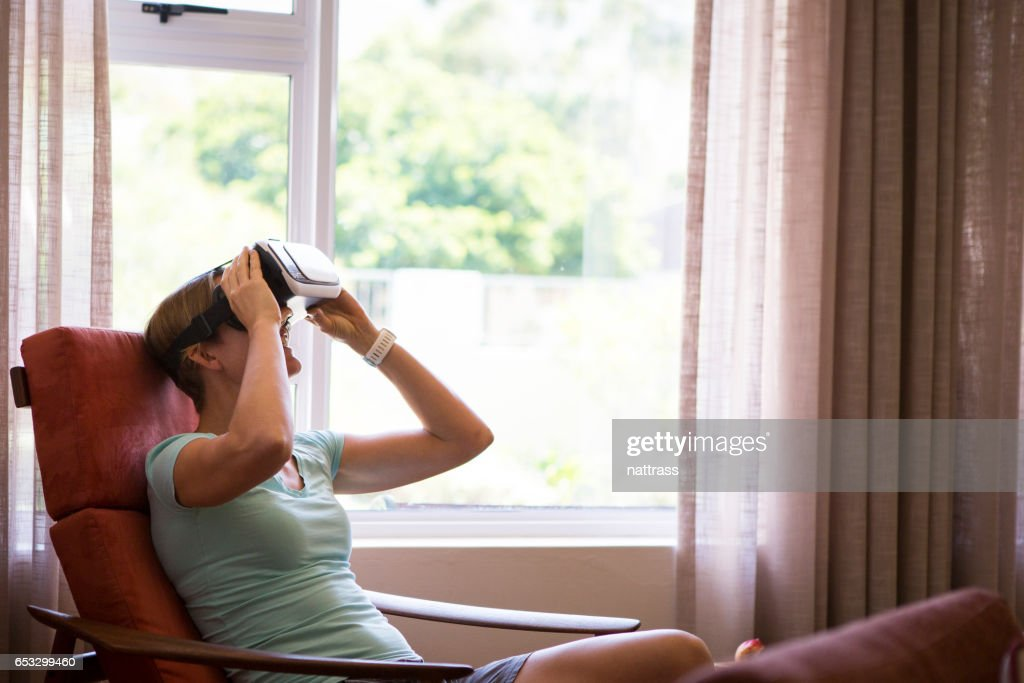 Mother enjoying some virtual reality fun at home : Stock Photo