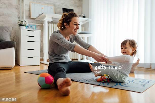 Mãe exercício com seu bebê em casa