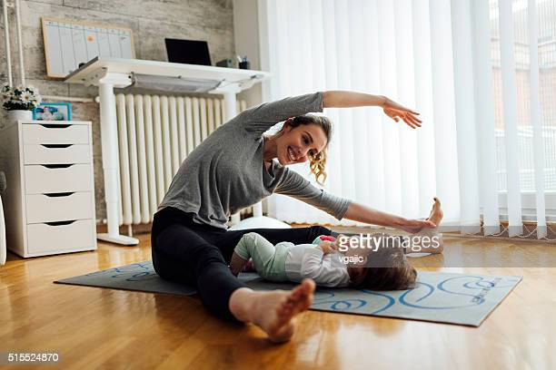 Mother Exercise With Her Baby At Home