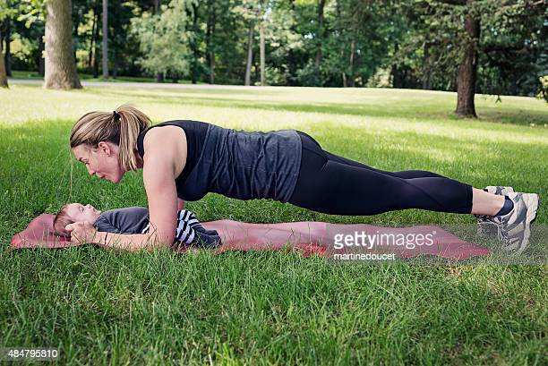 Mother exercising with baby in park in summer.