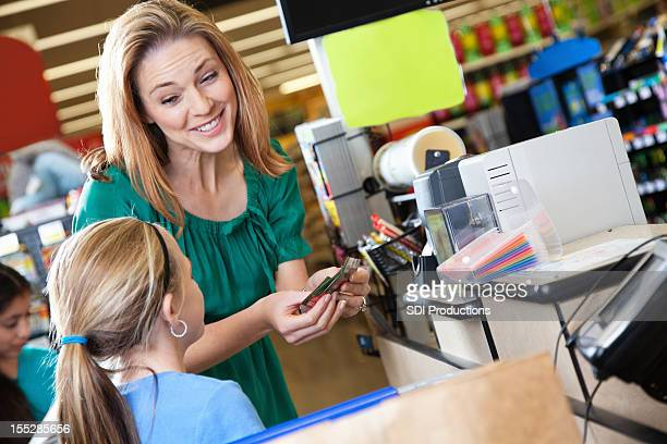 Mother explaining budgeting and couponing to daughter at supermarket