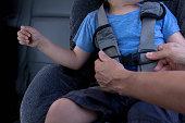 Mother fastening child safety seat belt in car