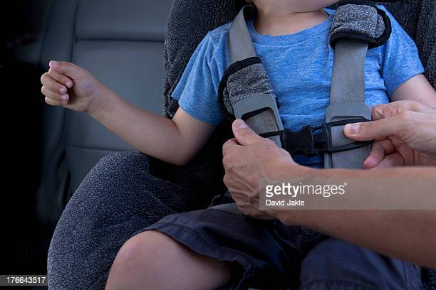 Mother fastening child safety seat belt in car