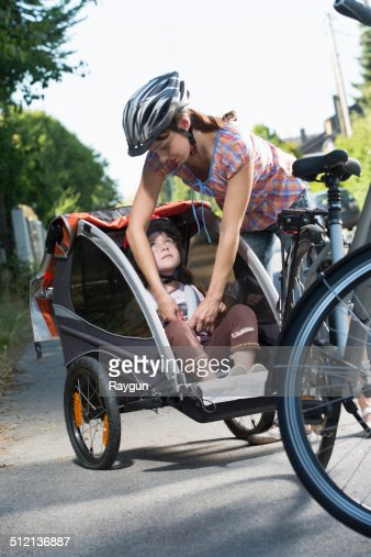 Mother fastening daughter's seatbelt in bicycle trailer