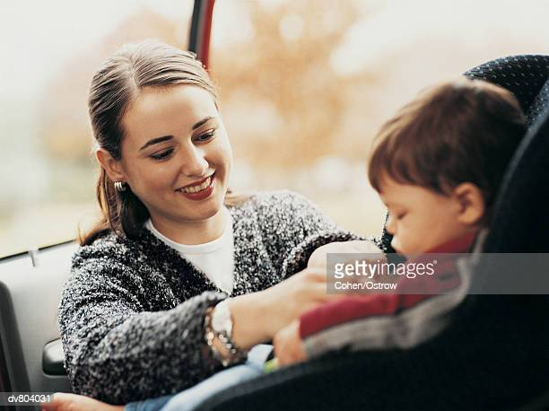 Mother Fastening her Toddler into Car