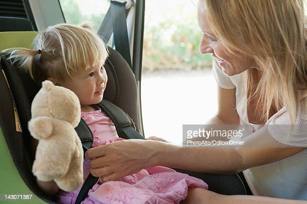Mother fastening little girl into car seat