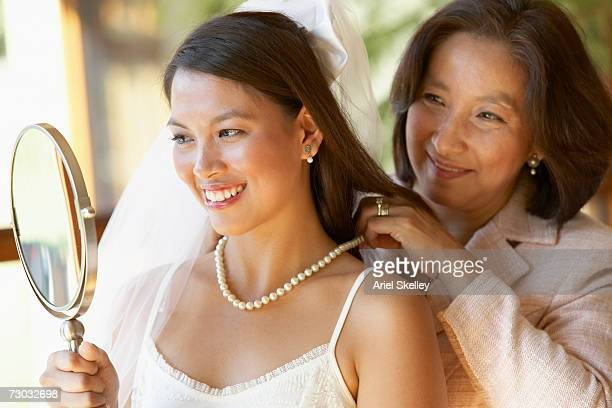 Mother fastening pearls necklace on bride looking at hand mirror