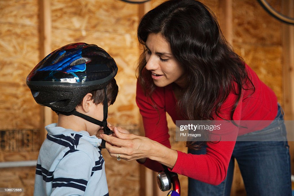 Mother fastening son's cycling helmet : Stock Photo