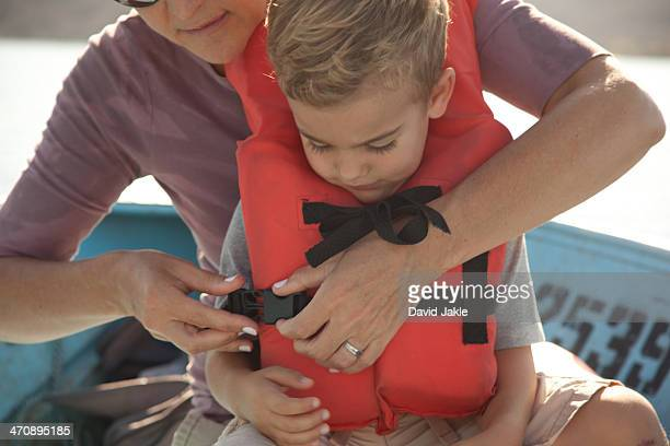 Mother fastening son's life jacket