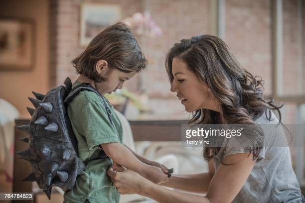 Mother fastening spiky backpack on son
