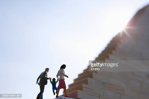 Mother, father and child figurines going up stairway, low angle view