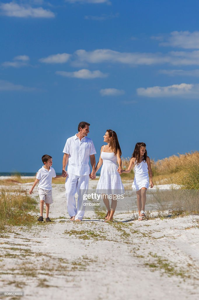 Mother, Father and Children Family Walking On Beach : Stock Photo
