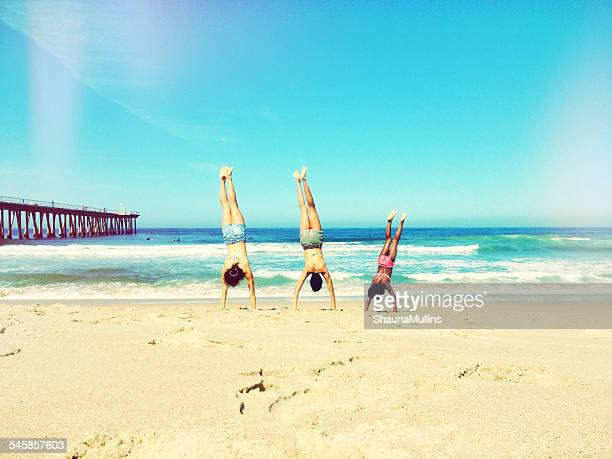 Mother, father and daughter doing handstand on beach