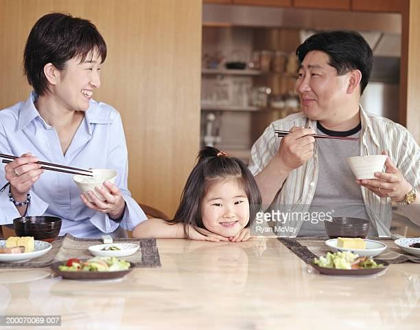 Mother, father and daughter (2-4) eating meal at home