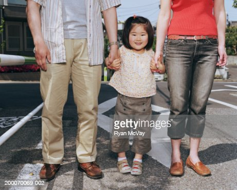 Mother, father and daughter (2-4) holding hands : Stock Photo