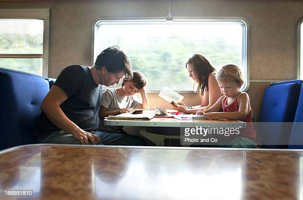 mother father and kids travelling by train