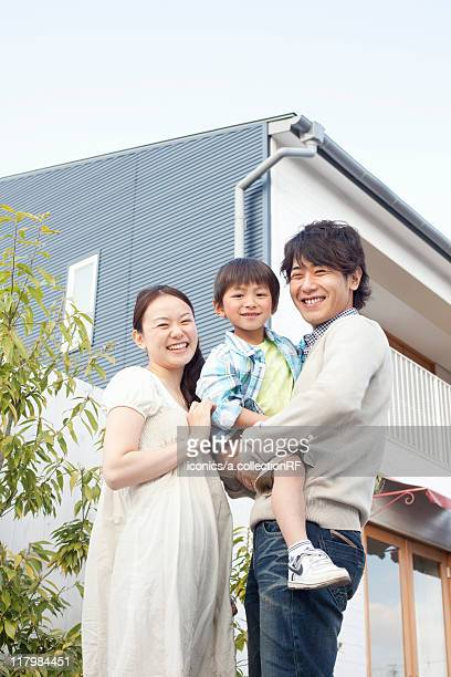 Mother, Father and Son Outside House