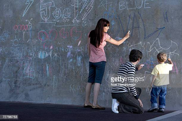 Mother, father and son (3-4 years) writing in chalk on wall