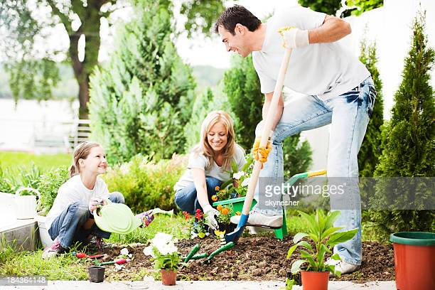 Mother, father and their daughter gardening.