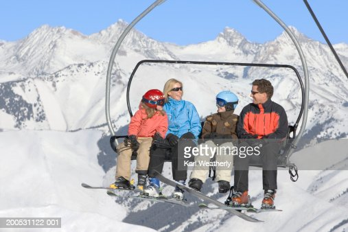 Mother, father and two children (8-10) sitting on ski lift