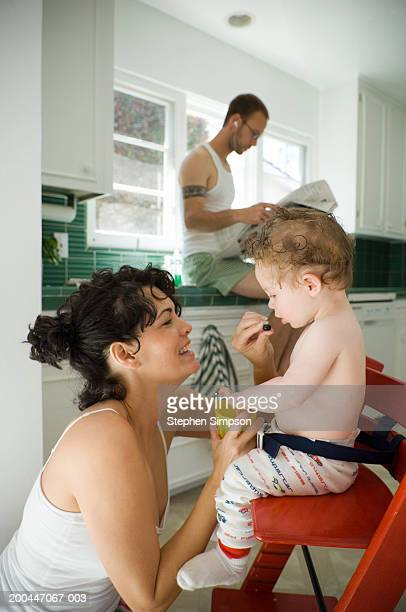 Mother feeding baby boy (9-12 months), father reading newspaper
