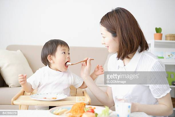 Mother feeding baby boy