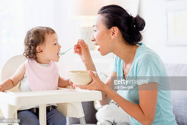 Mother feeding baby daughter in high chair